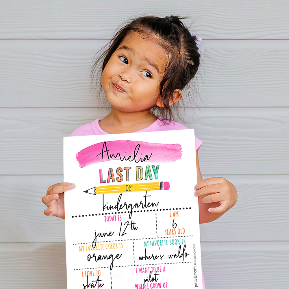 girl in pink dress holding last day of school sign